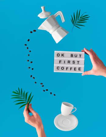 """Lévitation à la mode. Ligne volante de grains de café entre la cafetière en céramique et la tasse à expresso. Feuille de palmier et tableau lumineux avec texte """"OK mais café d'abord"""" dans les mains. Fond bleu menthe avec des feuilles de palmier."""