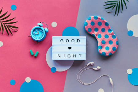 Healthy night sleep creative concept. Sleeping mask, blue mint alarm clock, earphones and earplugs. Two tone pink and silver background with paper circles. Flat lay, lightbox with text Good night.