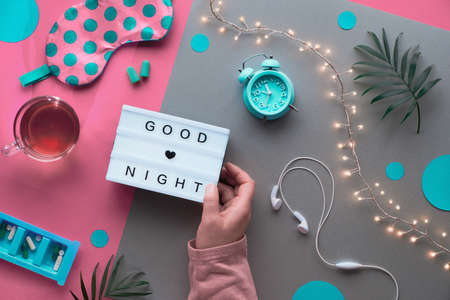 Healthy night sleep creative flat lay. Sleeping mask, blue mint alarm clock, earphones, earplugs. Two tone pink silver background with circles and palm leaves. Lightbox with text Good night in hand.