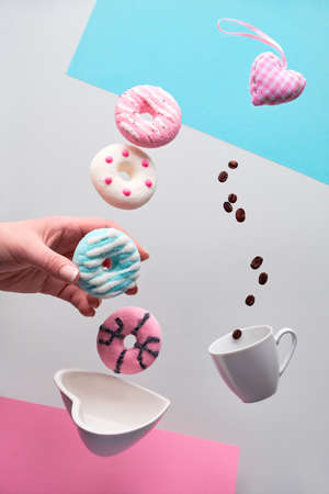 St. Valentine concept, levitation of doughnuts above heart shaped bowl. Coffee beans fly in espresso cup. Hand hold blue doughnut. Creative background in pastel colors - pink, blue and silver grey .