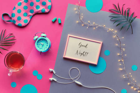 Frame with text Good night. Healthy night sleep creative flat lay. Sleeping mask, blue mint alarm clock, earphones, earplugs and tea. Split pink and silver background with circles and palm leaves