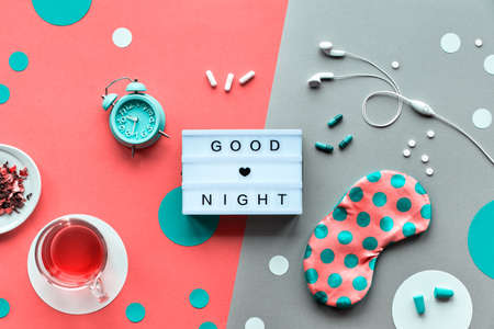 Text Good night on trendy lightbox. Pink sleeping mask with polka dots, alarm clock, earphones and earplugs. Pills, capsules and calming tea. Flat lay, two tone orange coral and silver background. Banco de Imagens