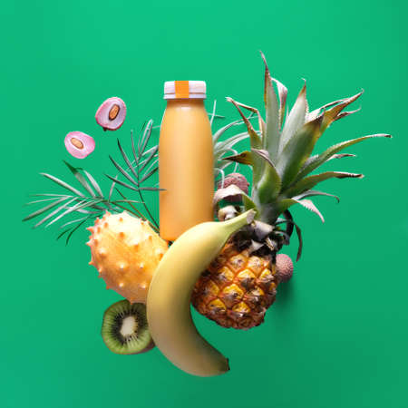 Assortment of tropical fruits around smoothie bottle on green background. Pineapple, kiwano, kiwi , lichee and banana - exotic fruits, square composition, levitation and balance.