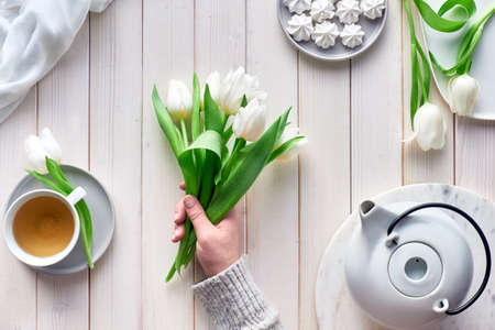 Spring celebration flat lay. Female hands with white tulips, sweets and tea on white wooden table. Spring celebration flat lay. Mother day, Valentine, international women day 8 or March or birthday.