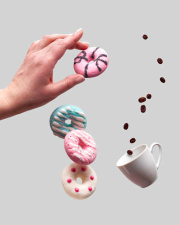 St. Valentine concept, levitation of doughnuts above heart shaped bowl. Coffee beans fly in espresso cup. Hand hold pink doughnut. Creative background on light grey color.
