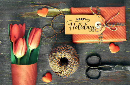 Wrapped gift with tag Happy Holidays, wrapping materials, scissors, checkered cord, hearts and red tulips on old rustic wooden table. Concept for preparation for Springtime holidays.