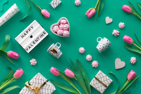 Geometric Valentine flat lay with Valentine's date February 14 on calendar, flowers, gifts, hearts, pink marshmallows and coffee cups. Valentine's day arrangement in white and gold on green background