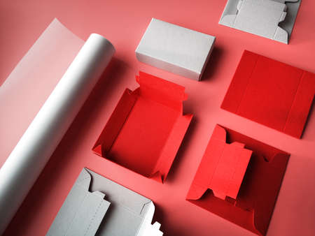 Creative crafts, pink background with roll of tracing paper, flat templates for flat cardboard gift boxes and ready box. Paper craft objects in pink, red and grey colors.