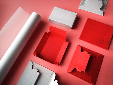 Manualidades creativas, fondo rosa con rollo de papel de calco, plantillas planas para cajas de regalo de cartón plano y caja lista. Objetos artesanales de papel en colores rosa, rojo y gris. Foto de archivo
