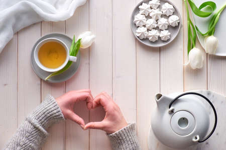 Spring celebration flat lay. Female hands show heart shape sign. Tea cup, tea pot, sweets and white tulips on white wooden table. Mother day, Valentine, international women day 8 March or birthday.