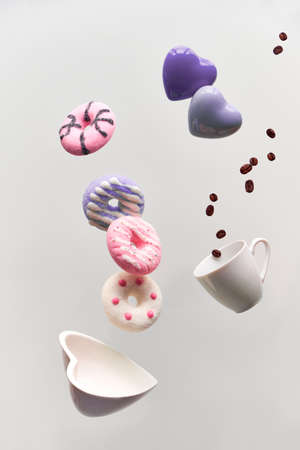 St. Valentine concept, levitation of doughnuts above heart shaped bowl. Coffee beans fly in espresso cup. Creative background in pastel colors on light grey color background