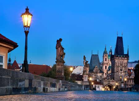 Charles Bridge at dawn, silhouette of Bridge Tower and saint sculptures with street light in Prague, Czech Republic Banco de Imagens