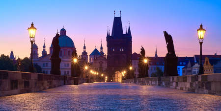 Charles Bridge at dawn in blue and purple, silhouette of Bridge Tower and saint sculptures with street lights in Prague, Czech Republic