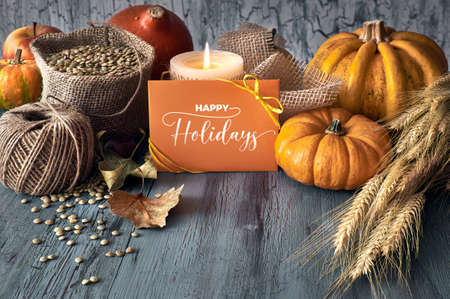 Autumn harvest still life with pumpkins, wheat ears and lentils in sackcloth sack with cord, candle and card on faded grey rustic wooden background. Paper card with text Happy Holidays. Фото со стока