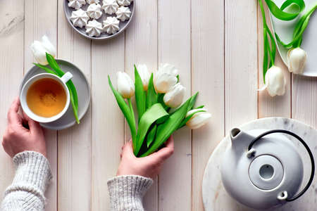 Spring celebration flat lay. Mother day, Valentine, international women day 8 or March, birthday, other special occasion. Female hands with tea and white tulips, sweets and tea on white wooden table.