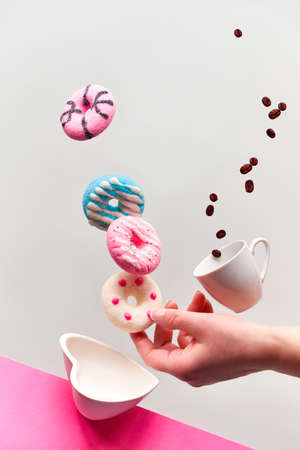 St. Valentine concept, levitation of doughnuts above heart shaped bowl. Coffee beans fly in espresso cup. Hand catching pink doughnut. Creative background in vibrant pink and light grey color.