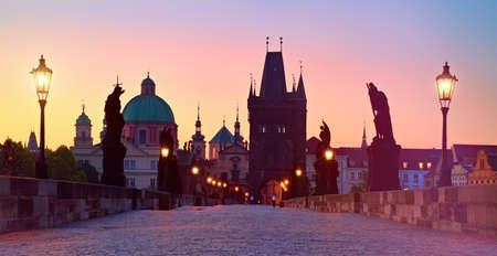 Charles Bridge at dawn, silhouette of Bridge Tower and saint sculptures with street lights in Prague, Czech Republic Banco de Imagens