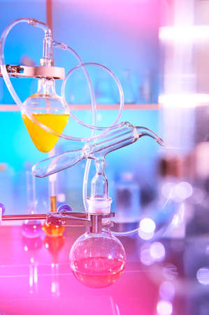 Reaction in progress in organic chemistry lab, distillation glassware, laboratory glass equipment. Futuristic neon lights, bold vibrant purple, pink, blue and turqiouse lights. Experiment in progress. Stock fotó