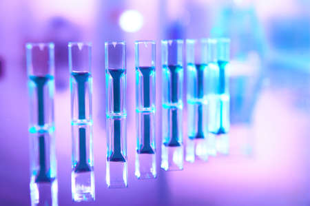Scientific background in vibrant neon, purple and blue. Pharma, biotech, protein analysis, protein concentration analysis, analytic chemistry. Spectrophotometer quvettes with reflection, copy-space. Banque d'images