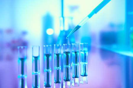 Contexte scientifique dans des couleurs néon vibrantes, violet, bleu et turquoise. Pharma, biotechnologie, analyse des protéines, mesure de la concentration en protéines. Quvettes de spectrophotomètre avec réflexion, espace de copie.
