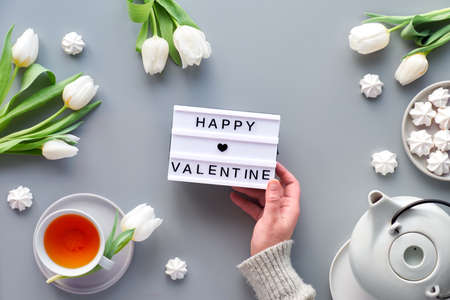 Happy Valentine text. Female hand holds lightboard.