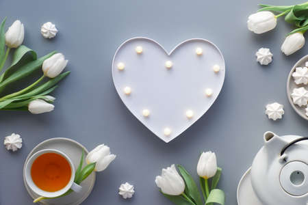 Heart shaped lightboard with lights, holiday decorations around. Tea pot, sweets and white tulips on silver grey background. Trendy modern flat lay, top view