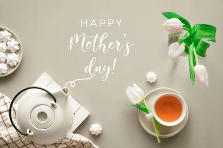 """Mother;s day tea and greeting text """"Happy Mother's day"""". Trendy modern table setup, flat lay, top view. Tea pot, sweets and white tulips on light beige neutral paper. Sweet marshmallows tasty snack."""