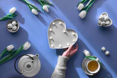 Female hand holding heart shape lightboard.