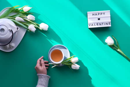 "Spring geometric flat lay. Female hands hold lightbox with text ""Happy Valentine"". Tea cup, pot, sweets and white tulips on green. Valentine's day, sunlight, long shadow design, top view"
