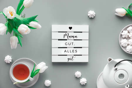 """Mother;s day tea and greeting text, flat lay. Tea pot, sweets and white tulips on light grey. Mothers day. Text """"Mama gut alles gut"""" in German means """"All is well when Mom is well"""". Sweet marshmallows"""