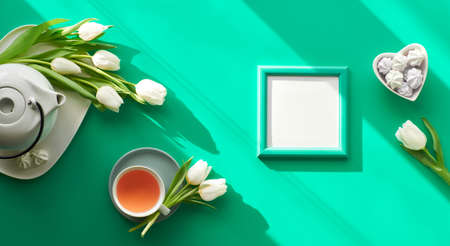 Spring geometric flat lay, panoramic. Tea cup, pot, sweets and white tulips on green. Valentine's day, Mother's day, international women day March 8. Diagonal sunlight, long shadows, trendy top view