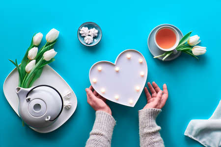 Spring celebration flat lay. Female hands show heart shape sign. Tea cup, tea pot, sweets and white tulips on blue table. Mothers day, international women day 8 March or your mom birthday.