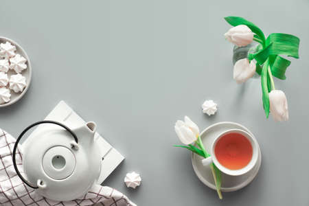 Geometric panoramic flat lay with hands. Cup of black tea, tea pot, sweets and white tulips on grey with copy-space.