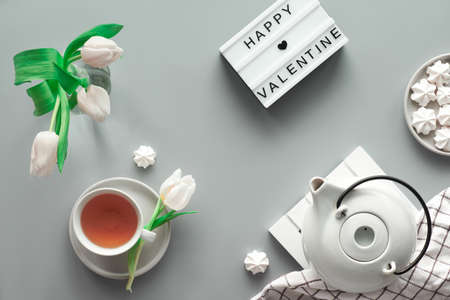 Geometric panoramic flat lay with hands. Cup of black tea, tea pot, sweets and white tulips on grey with lightboard.