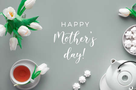 """Mother;s day tea and greeting text """"Happy Mother's day"""". Trendy modern flat lay, top view. Tea pot, sweets and white tulips on light grey. Sweet marshmallows tasty snack."""