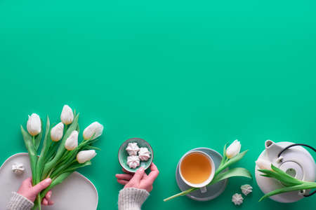 Geometric panoramic flat lay with hands. Cup of black tea, tea pot, sweets and white tulips on green with copy-space.