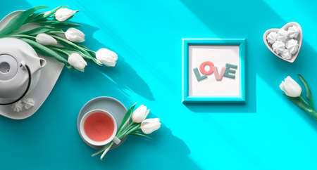 """Spring geometric flat lay. Female hand hold frame with text """"Love"""". Tea cup, pot, sweets and white tulips on turquoise. Mothers day, international women day 8 March or your Mama birthday."""