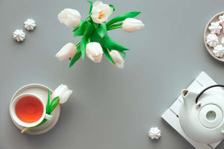 Mother;s day tea table set. Trendy modern flat lay, top view. Tea pot, sweets and white tulips on light silver grey paper.
