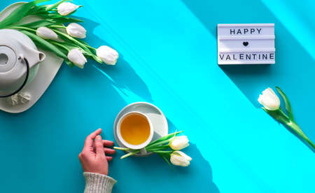 Spring geometric flat lay. Female hand holding tea cup. Tea pot, sweets and white tulips on turquoise panoramic background. Mothers day, international women day 8 March or your Mama birthday.