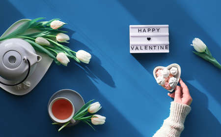 Happy Valentine day celebration flat lay. Female hands show heart shape sign. Tea cup, tea pot, sweets and white tulips on tale, background in trendy classic blue color.