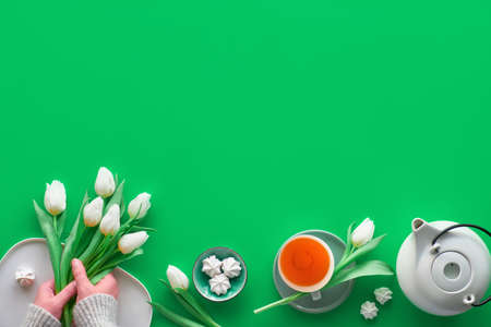 Geometric panoramic flat lay with hands. Cup of black tea, tea pot, sweets and white tulips on green with copy-space. Valentine, Mother's day, international women day March 8. Trendy flat lay.