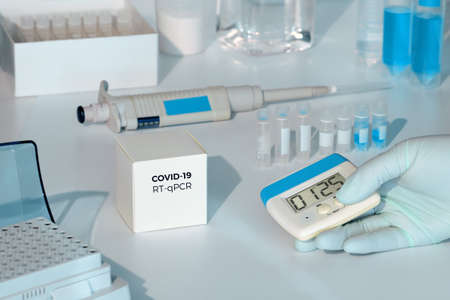 Quick novel COVID-19 coronavirus test kit. 2019 nCoV pcr diagnostics kit. Hand in glove with timer. RT-PCR kit to detect covid19 virus in clinical samples. Тest based on real-time PCR methodology.