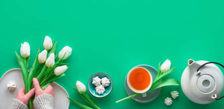 Geometric panoramic flat lay with hands. Cup of black tea, tea pot, sweets and white tulips on green with copy-space. Valentine, Mother's day, international women day March 8. Top view, panoramic image