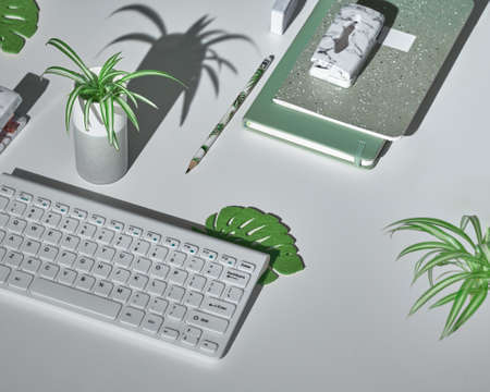 Concept background with modern office supplies in white, mint green and marble. Isometric projection, geometric layout with tropical leaves. Notebook, stapler, keyboard, mouse, stapler, hole puncher.