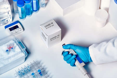 Novel coronavirus 2019 nCoV pcr diagnostics kit. Hand in glove with automatic pilette. RT-PCR kit to detect 2019-nCoV or covid19 virus in clinical samples. Тest based on real-time PCR technology