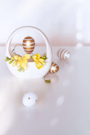 Easter golden stripy egg with polka dots and yellow freesia flower, great design for any purposes. Interior Spring design ideas for home decor. Greeting Easter card, poster, banner, background
