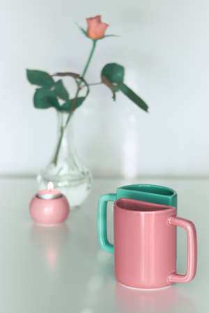 Pink rose flower and twin half tea mugs in salmon pink and fresh mint green. Minimalist design for your house in pastel colors. Modern interior decor, romantic gifts. Design for greeting card.