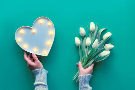 Mother's day, international women day March 8. Trendy ornamental modern background. Flat lay with hands holding plastic heart shaped lightboard with lights and bunch of white tulips