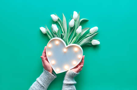Geometric panoramic flat lay with hands holding plastic heart shaped lightboard with lights and bunch of white tulips. Mother's day, international women day March 8.
