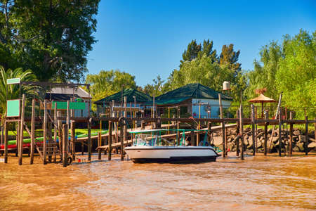 Tigra delta in Argentina, river system of the Parana Delta North from capital Buenos Aires. Lush vegetation, wooden houses. Motor boat by wooden pier. Orange clay water of Rio de la Plata delta system